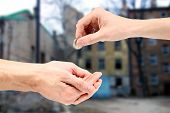 stock photo of pity  - Hand gives coin to beggar on the street - JPG
