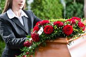 image of burial  - Mourning woman on funeral with red rose standing at casket or coffin - JPG