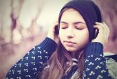 Teenage Girl In Headphones Listens To Music With Closed Eyes poster