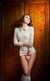 picture of playmate  - Beautiful brunette woman in white sensual lace outfit posing provocatively in front of a wooden wall - JPG