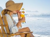 stock photo of strawberry blonde  - Smiling blonde relaxing in deck chair by the sea sipping cocktail on a sunny day - JPG
