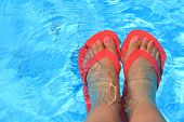 stock photo of wet feet  - Female feet with flip flops in water - JPG