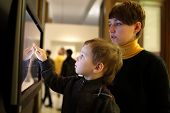 foto of realism  - Family playing with touch screen in a museum - JPG