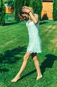 pic of tramp  - girl in a dress joyfully walks the tramp on a green grass on a country site - JPG