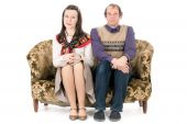 stock photo of old couple  - bored old looking couple sitting on vintage couch isolated on white - JPG