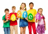 picture of card-making  - Children holding egg shape colourful cards with letters in a row making word Easter together - JPG