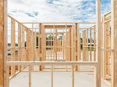 picture of framing a building  - New residential construction home framing against a blue sky - JPG