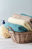 stock photo of bath sponge  - Bath towels of different colors in wicker basket on light background - JPG