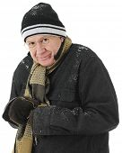 stock photo of shivering  - Closeup image of a bundled but shivering senior man smiling at the viewer - JPG