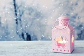 stock photo of kerosene lamp  - Lantern on wooden table on winter background - JPG