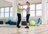 stock photo of personal assistant  - Female trainer helping senior woman standing on a balance board at gym - JPG