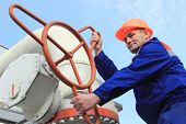stock photo of turn-up  - Worker turns valve on gas compressor station bottom view close - JPG