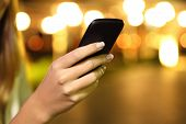 foto of ladies night  - Close up of a woman hand using a smart phone in the night with lights in the background - JPG