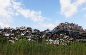 stock photo of junk-yard  - Scrap yard with crushed cars and blue sky  - JPG