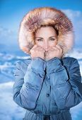Closeup portrait of cute female outdoors in winter time, wearing stylish casual blue coat with furry hood, winter fashion concept poster