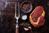 picture of ribeye steak  - Raw fresh meat Ribeye Steak seasoning and meat fork on dark background - JPG