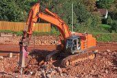 image of breaker  - rock breaker working on a road construction site - JPG
