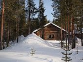 pic of chalet  - Romantic snow covered wintersport chalet between the pine trees in a holiday resort in Lapland Finland - JPG