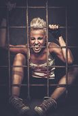 stock photo of delinquency  - Troubled teenager girl behind bars - JPG