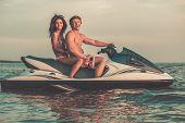 stock photo of jet-ski  - Multi ethnic couple sitting on a jet ski - JPG