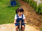 pic of seesaw  - 2-year-old Asian-Caucasian girl plays on a seesaw