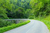 stock photo of naturel  - Sharply curved dowhhill winding road in the Pyrenees in Boussenac in France - JPG