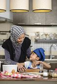 picture of hijabs  - Moslem woman wearing hijab teaching her daughter make halal food - JPG