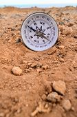 stock photo of orientation  - Orientation Concept Metal Compass on a Rock in the Desert - JPG