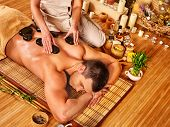 image of stone-therapy  - Man getting stone therapy massage in bamboo spa - JPG