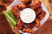 stock photo of chicken wings  - bbq buffalo chicken wings with beer ranch and celery shot top down - JPG