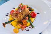 stock photo of pork belly  - Crispy pork belly on kabocha squash puree with tomatoes and asparagus topped with pico de gallo - JPG