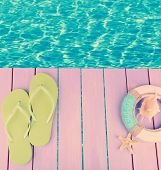 pic of beside  - Colored flip flops on wooden platform beside sea - JPG