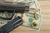 picture of corruption  - detail of gun with bullet on US dollar banknotes crime or corruption concept - JPG