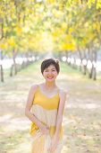 foto of emotions faces  - portrait of young beautiful asian woman wearing yellow long dress with smiling face happiness emotion standing in flowers blooming park vertical form - JPG