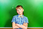 stock photo of schoolboys  - Smart schoolboy stands at the blackboard in the classroom - JPG