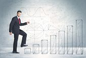 pic of climb up  - Business man climbing up on hand drawn graphs concept on background - JPG