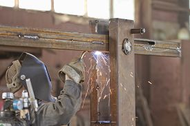 picture of gases  - Welder brews metal structure in the shop - JPG