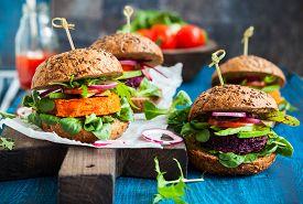 stock photo of veggie burger  - Veggie beet and carrot burgers with avocado - JPG