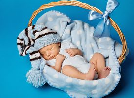 stock photo of birthday hat  - Newborn Baby Inside Basket New Born Kid Dream in Woolen Hat Little Child Boy Sleeping over Blue Background - JPG