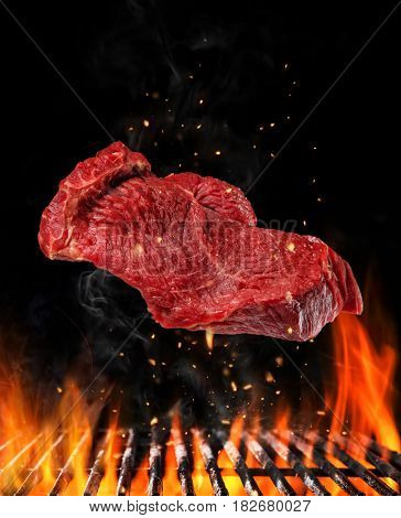 Flying raw steak above barbecue