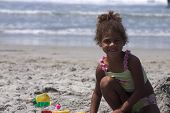 stock photo of black american  - a young pretty girl plays in the sand at the beach - JPG