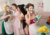 stock photo of foursome  - Woman on phone while friends give young woman cigarette and alcohol in a retro styled kitchen scene - JPG