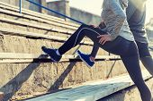fitness, sport, exercising and lifestyle concept - close up of couple stretching leg on stands of st poster