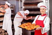 A female baker holding freshly baked croissants in bakery