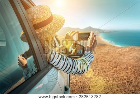 poster of Happiness young woman traveler sitting in white car and shoot with her phone camera beautifull ocean