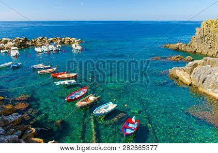 poster of Fishing Colorful Boats On Transparent Water In Small Harbor Of Riomaggiore Village National Park Cin