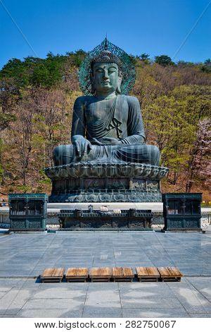 poster of The Great Unification Buddha Tongil Daebul is a 14.6-meter 108 ton Bronze Buddha statue in Seoraksan
