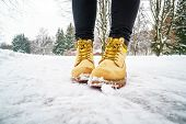 Winter Walk In Yellow Leather Boots. Front View On The Feet Of A Man Walking Along The Icy Snowy Pav poster