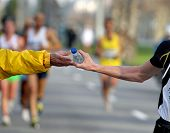 stock photo of long distance  - Runner take a bottle of water in a long distance race - JPG
