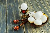 White Egg In Wooden Stand, Eggs In Wooden Colorful Dish And Wooden Painted Spoons On Rough Old Woode poster